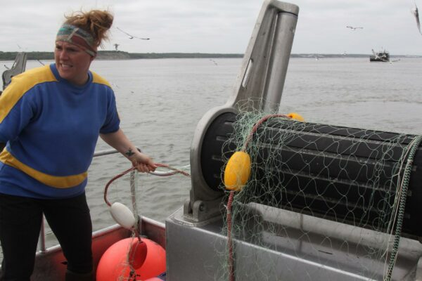 A woman pulls a net out on the deck of a boat.