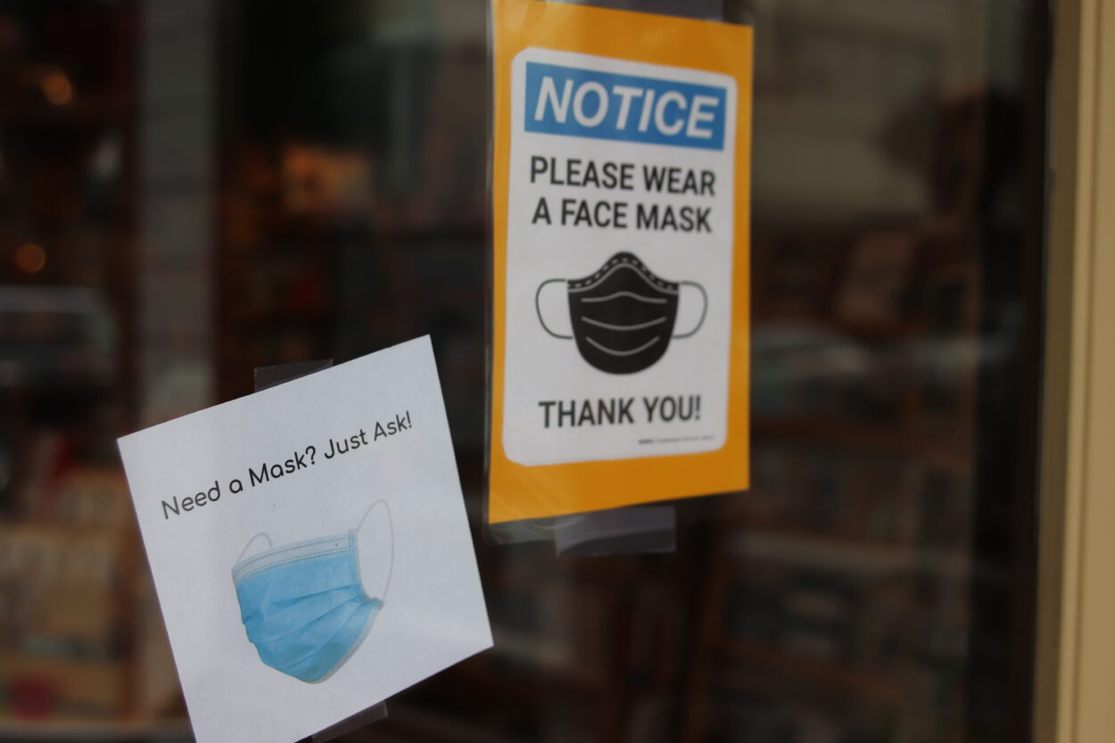 Two signs on a glass door ask customers to wear a face mask.