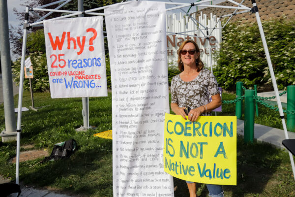 """A white woman in a dress holds a yellow sign that says """"Coercion is not a native value"""""""