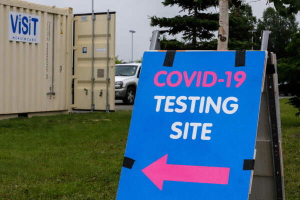 """a shipping container and a sign that reads """"COVID-19 TESTING SITE"""""""
