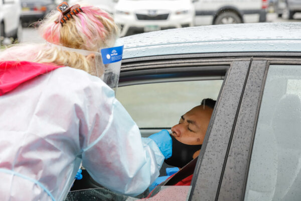 a medical professional swabs a driver's nostril