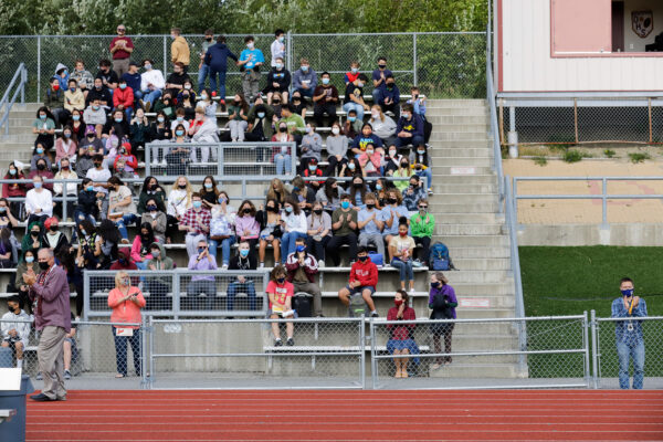 a group of people in the stands above a track & field
