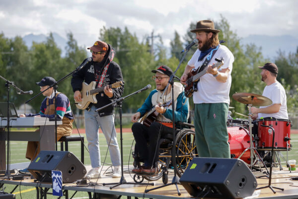 a group of people perform music on stage on a football field