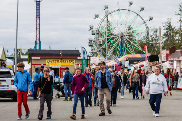 People walk through the Alaska State Fair grounds in Palmer - some masked, some not. Ferris wheel in the background