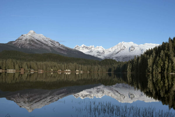 A photo of a lake with snowy mountains in the backdrop. A reflection of the mountains is also visible in the lake.
