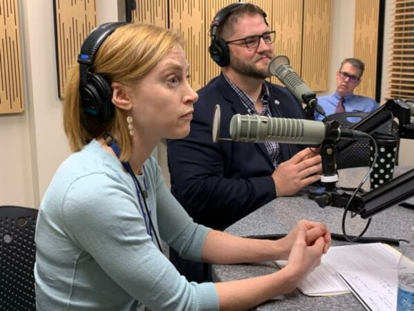 A woman and a man are talking into microphones in a room, both wearing headphones.