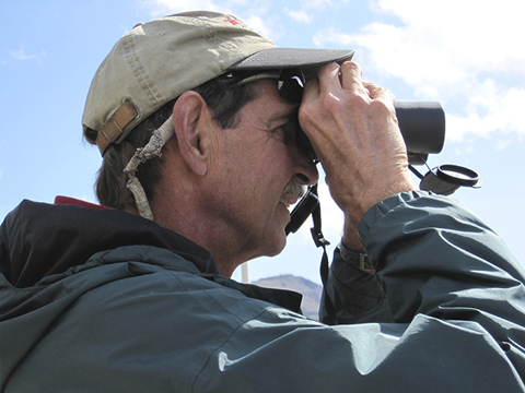 A man in a cap and jacket looks through binoculars.
