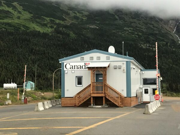 A white and blue building in the middle of the road that says Canada on the side.