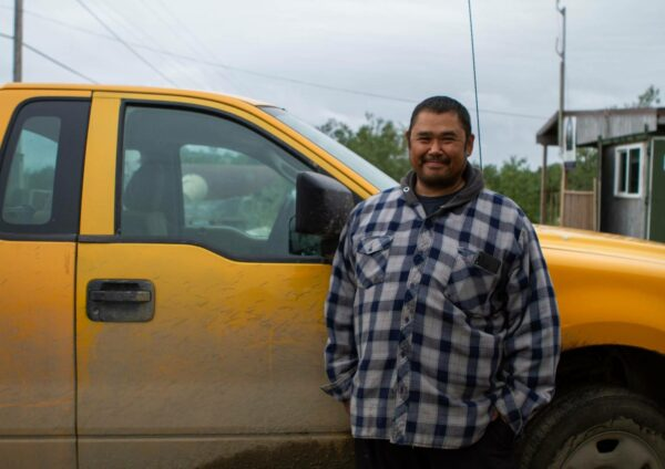 A ma in a plaid shirt stands next to a yellow pickup truck