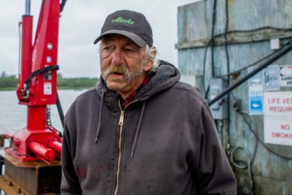 A man with a black cap that says Alaska on and a black zip-up hoodie looks off into the distance.