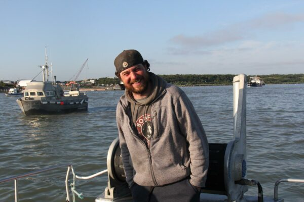 A man in a hat and a sweatshirt smiles on the deck of a boat.