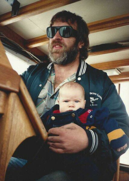 A baby sits on a man's lap who is wearing sunglasses and steering a boat.