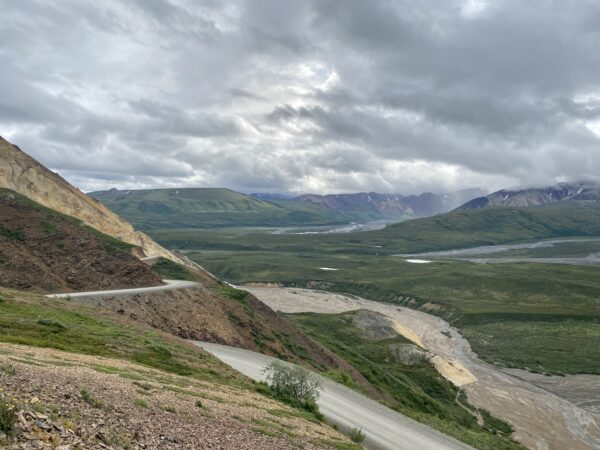 A narrow road cuts through valleys and mountains.