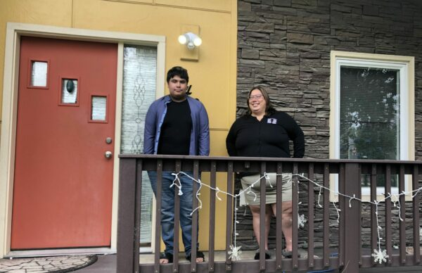 A teenage boy stands on the porch of his house. The porch is brown and the house has a red door with a wide yellow border. The boy is standing next to his mother who is staring at him with a smile as the picture is being taken.