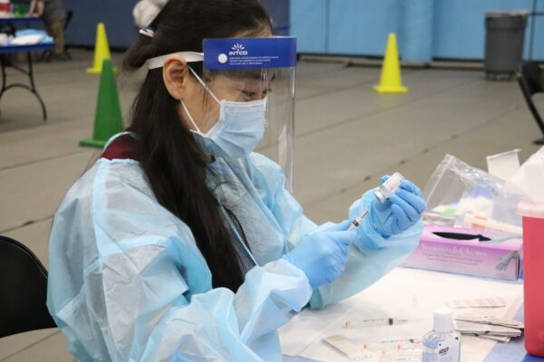 A woman filling a vial in a face mask and shield.