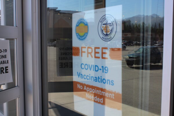 """A sign taped in a window that says """"Free COVID-19 vaccinations/No Appintment Needed)"""