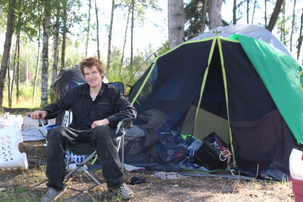 A man dressed in black sits in a lawn chair in front of his tent