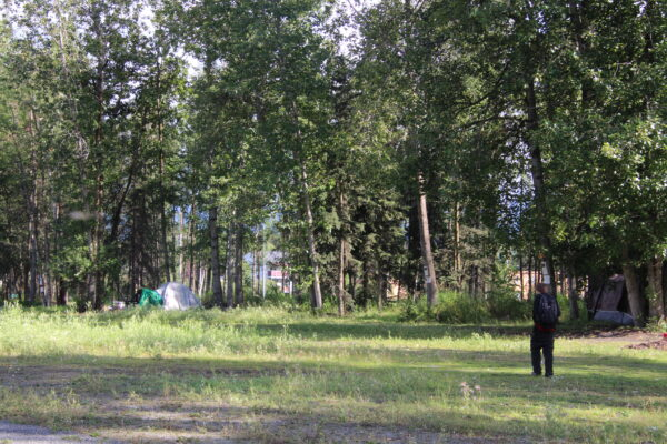 A man in black walks towards a tent in some trees