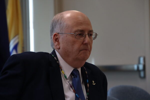 A white man in a black suit and glasses stares straight ahead in a conference room