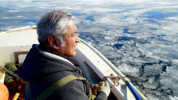 A man wearing a jacket in a boat looks out over sea ice.
