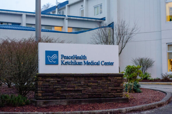 A white and blue sign outside of a multi-story white and blue medical building.