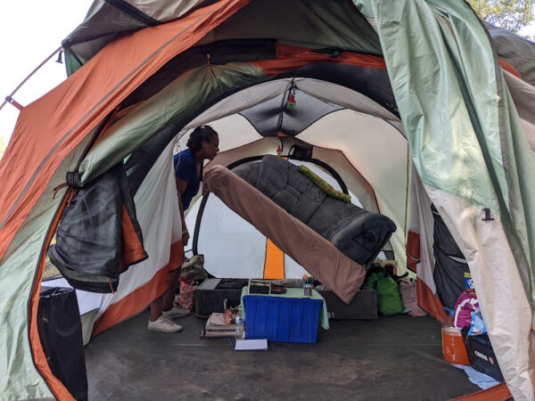 A woman lifts up a  bed inside a clean tents