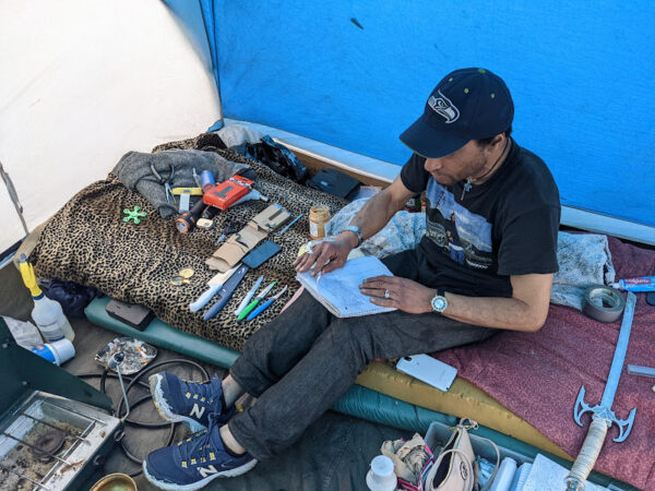 A man sits on a bed with a bunch of knives and other tools and leafs through a white notebook