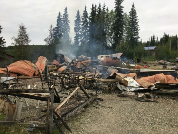 smoldering debris from a fire sits in front of green spruce trees.