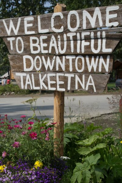 """A wooden sign reads """"Welcome to beautiful downtown Talkeetna."""""""