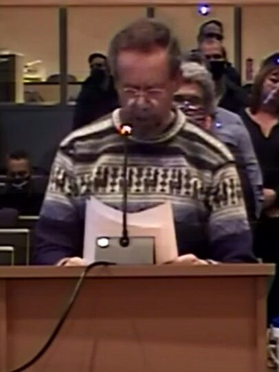 A white man in a patterned wool sweater speaks into a microphone at a podium