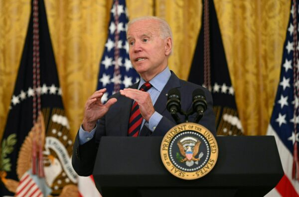 A man in a suite gestures with his hands behind a podium.