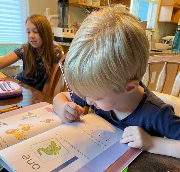 A toddler boy with blonde hair works in a workbook at a table next to an older girl with brown hair also doing school work at the table.