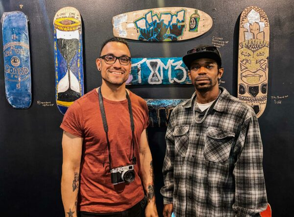 two people pose in front of painted skateboards in an art gallery