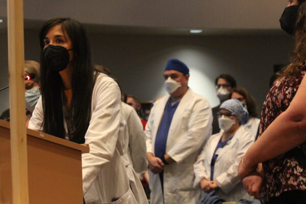 woman in lab coat and mask stands at podium with others behind her.