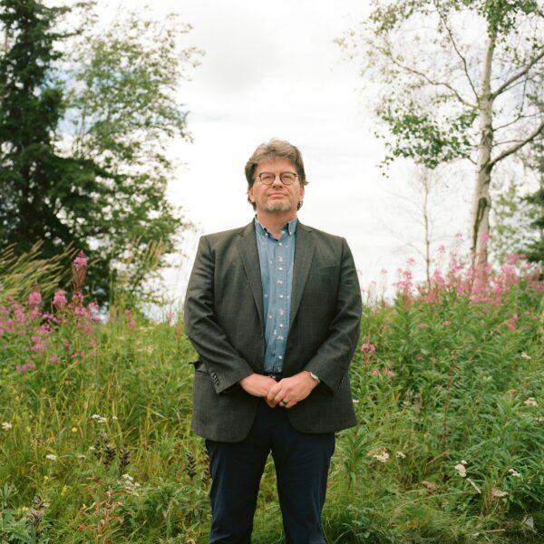 Man in suit coat standing in fireweed