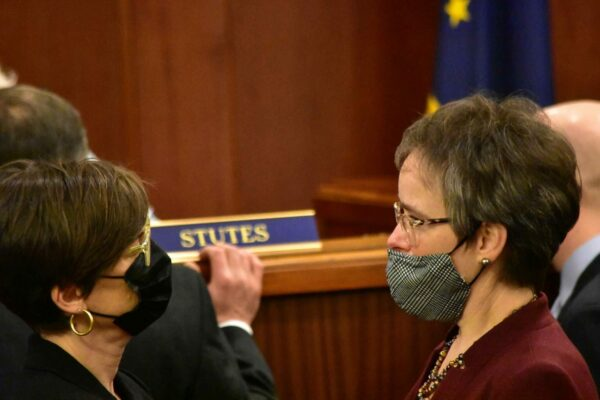Two masked women on the floor of the state legislature