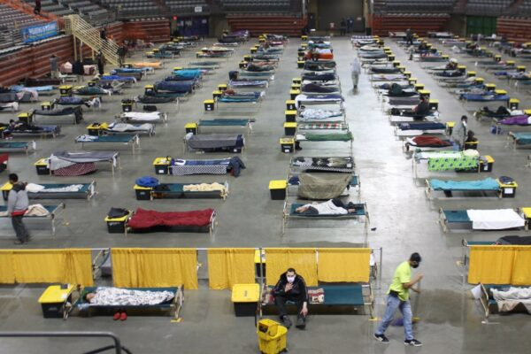 a view of the Sullivan Arena shelter floor with a number of cots and people in masks spread throughout