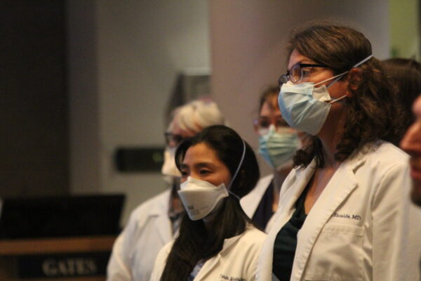 Woman in white jackets and masks stand in a line.