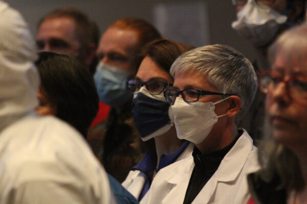 People wearing masks, some in white jackets, stare athead.