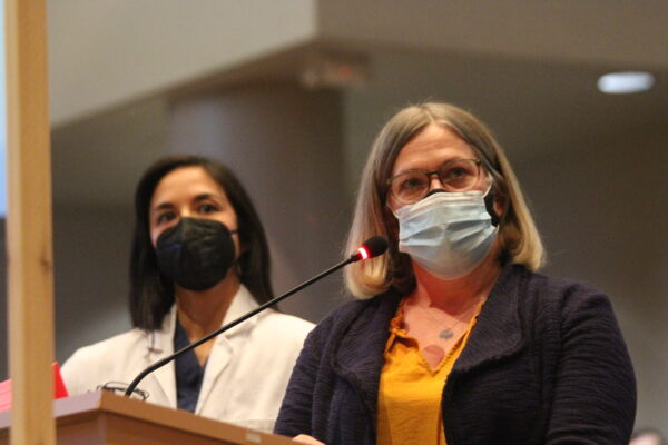 Two women in masks standing at a podium