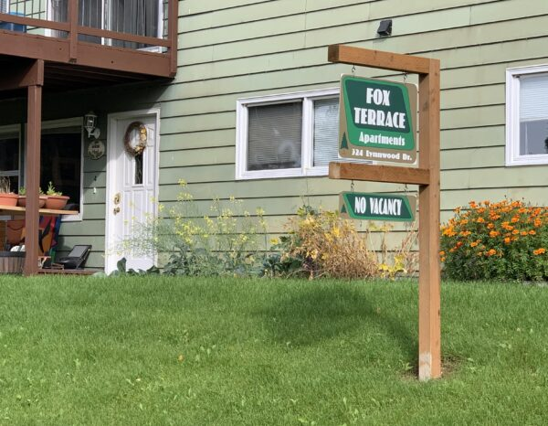 """A sign reads """"Fox Terrance Apartments: No vacancy"""" outside of a green-colored building."""