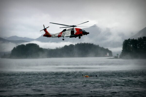 A red and white plane flies over water, above someone in the water.