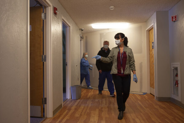 A woman wearing a mask and gloves leads two other people through a hallway.