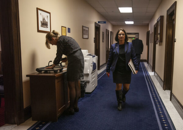 A woman in a dress and boots walks down a hallway.