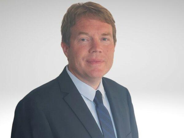 A portrait photo of a man wearing a suit.