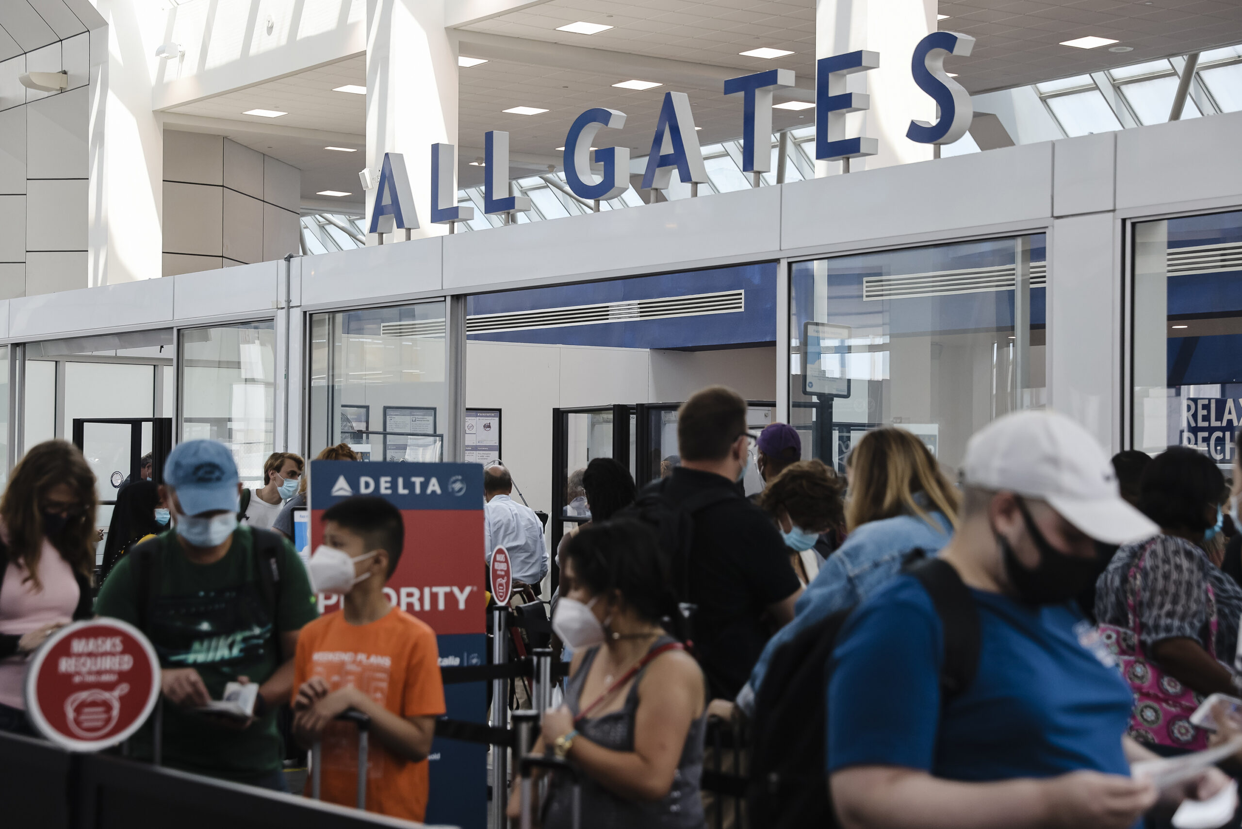 """People stand in line around a sign that says """"All Gates"""" wearing masks."""