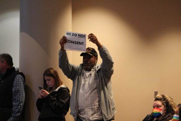 A person holds a sign saying I will not consent