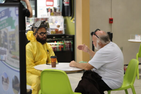 A person in a yellow hazmat suit and facemask sits at a tale with a white man in a white tshirt