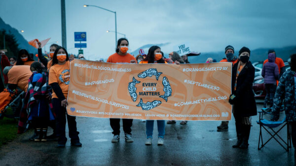 """People holding orange banner that says """"every child matters"""""""
