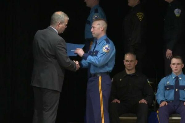 A man in a troopers uniform shakes another man's hand while getting a diploma.